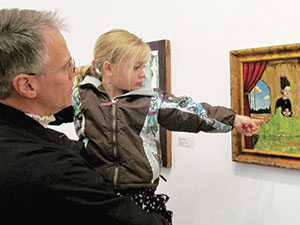 Four-year-old Vienna Reichert of Somerville checked out a painting at the Brickbottom Open Studios last weekend, accompanied by her dad Christopher.~Photo by Elizabeth Sheeran
