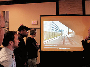 Attendees at the Green Line Extension meeting at the Holiday Inn last week viewed a 3D presentation depicting the Green Line route from Lechmere to Union Square stations. ~Photos by Douglas Yu