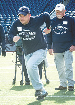 U.S. Army Veteran Frank Ellis sprints onto the field at Gillette Stadium for a running drill. He is joined by U.S. Air Force Veteran Paul O'Connor of Raynham, MA.