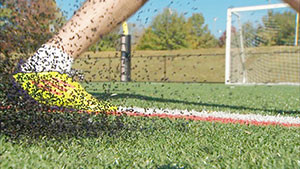 Crumb rubber sprays when artificial turf is struck with a falling ball, foot, or human.