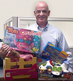 Michael McWilliams, Middlesex Federal Loan Officer and Somerville Kiwanis President, places his toy donation into the Middlesex Federal's Davis Square Toys for Tots collection box.