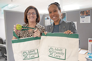 Jeanne Leyden (left) and Melissa Guevara display items from the caregiver appreciation packages that Adult Family Care is distributing as part of National Family Caregivers Month. The program serves more than 250 caregivers across the Greater Boston Area. ~ Photo by Nathan Lamb